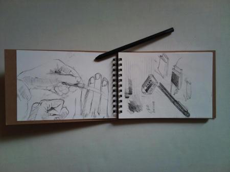 両手を広げたくらいの大きさの小さいクロッキー帳に、黒い木炭鉛筆で人間の手の落書きを描いた画像。見開きに開いたクロッキー帳の上に、黒いチャコールペンシルを乗せた状態で撮影されている。