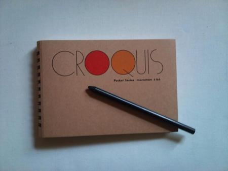表紙の閉じられた小型のクロッキー帳とチャコールペンシルを白い台の上に置き、真上から撮影した写真。クロッキー帳の茶色い表紙と、真っ黒なチャコールペンシルが写っている。