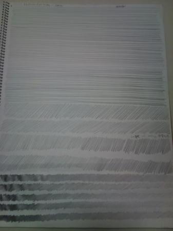 画用紙ほどの大きさのクロッキー帳を開き、正面から撮った写真。金属のリングで綴じられた白い紙に、水平でまっすぐな直線や、斜めの短い直線など3種類の鉛筆線が多数描かれている。