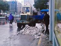 ショベルカーで雪をトラックへ積んでる様子