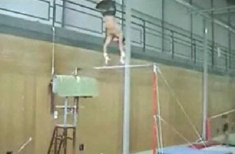 鉄棒から落下する体操選手