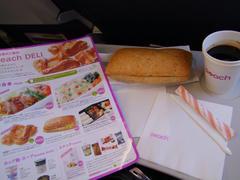 機内のメニューと、頼んだサンドイッチとコーヒー