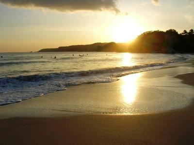 海と夕陽とサーファー