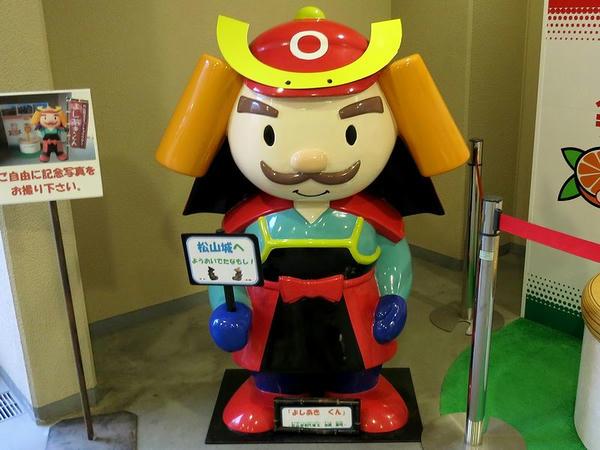 「松山城へようおいでたなもし!」の看板を持つよしあきくん