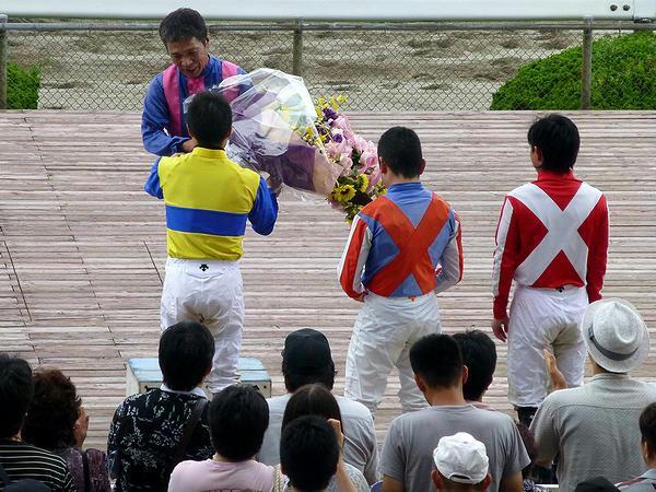 引退式で平瀬騎手から花束を受け取る山中利夫騎手
