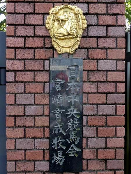 門柱に掲げられた「日本中央競馬会宮崎育成牧場」のプレートとエンブレム