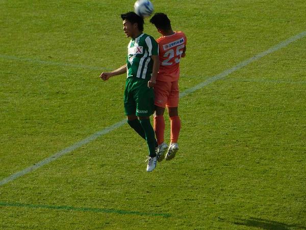 空中でハイボールを競り合う両軍選手