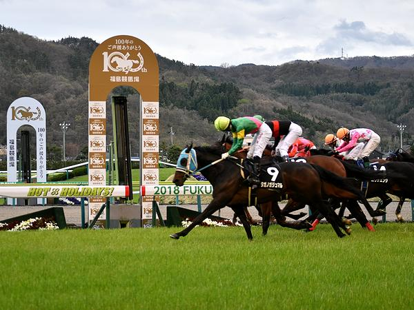 福島競馬場開設100周年記念のゴール板を過ぎる競走馬たち