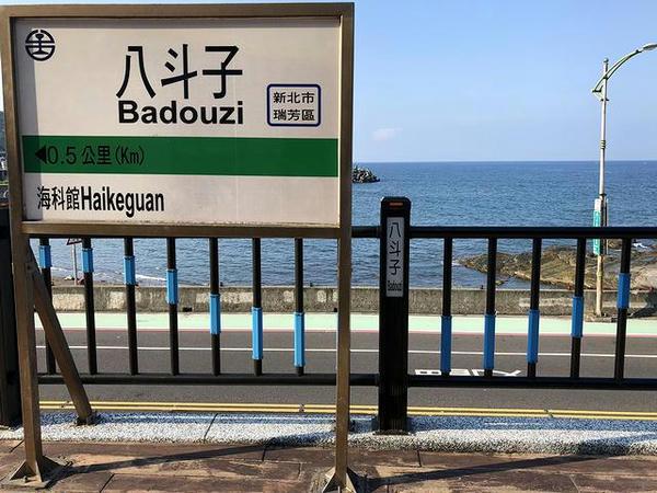 八斗子駅の駅名標と海