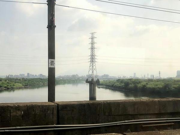 車窓から見た河川の中の高圧鉄塔