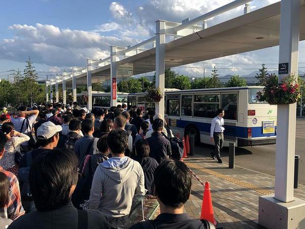二十四軒駅行きの無料送迎バスに乗り込む人々