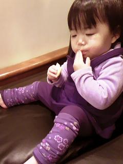 カリモク60のソファ上で赤ちゃんせんべいを味わう赤子