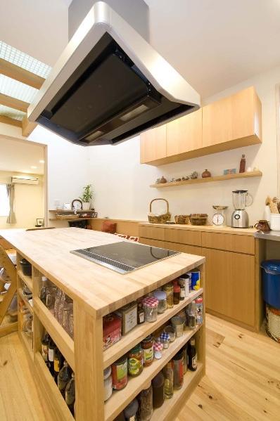コンロとダイニングテーブルを一体化させたキッチンはカバザクラの造作。コンロの下部分には料理に使う調味料や材料をすぐに取り出せるよう棚を設けた。収納力たっぷりの吊り戸棚や食器棚もカバザクラ。床はフレンチパインの無垢材に、木目を楽しめるクリアのオイルを。