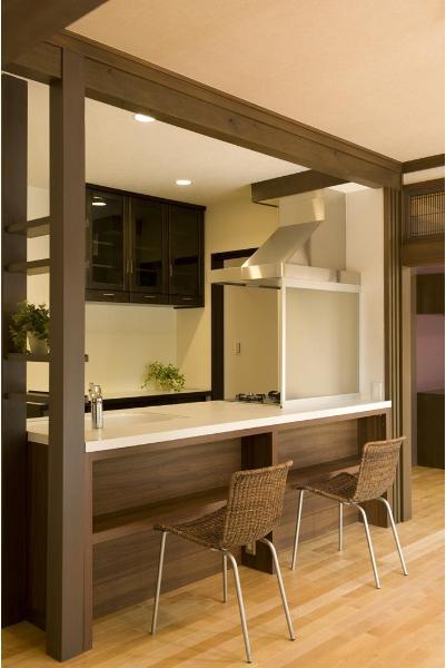 家族が自然と集まる、キッチンを中心とした心地よいリビングに。広々としたカウンターキッチンはINAX製。カウンター下の収納部分に合わせ、周囲の柱や梁を同じ色合いで塗装。一体感を持たせた。キッチンに取り付けられた棚は、既存の食器棚を上下に分けて再利用している。