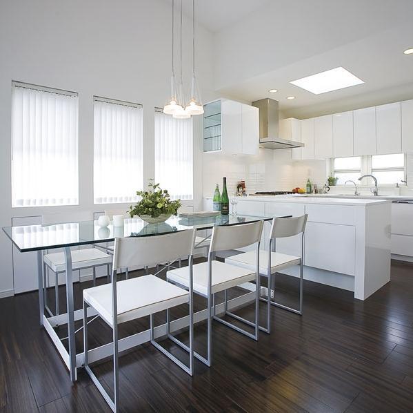 色数を抑え、統一感にこだわってシャープでモダンなデザインに一新。以前、キッチンとダイニングの間には吊り戸棚の下に小さな開口部があるのみだったが、壁を撤去して開放感のあるオープンキッチンに変えた。キッチンはL型からコの字型に変更し、ダイニングの収納はキッチンと面材を揃える配慮も。