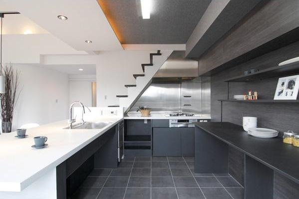 奥様の好みに合わせて造作されたキッチン。右側の内壁にはリビングの床材の木目のラインが映える素材を用い、グラデーションのような美しさを表現した。