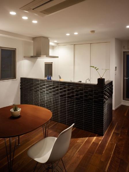 キッチンカウンターは2種類の黒いタイルを張り分け、個性的に演出。背面には大きな収納を設けて収納量を確保しつつ、白で壁と同化させることで、キッチンの明るさやDKにおける黒いカウンターの印象をさらに引き立てている。