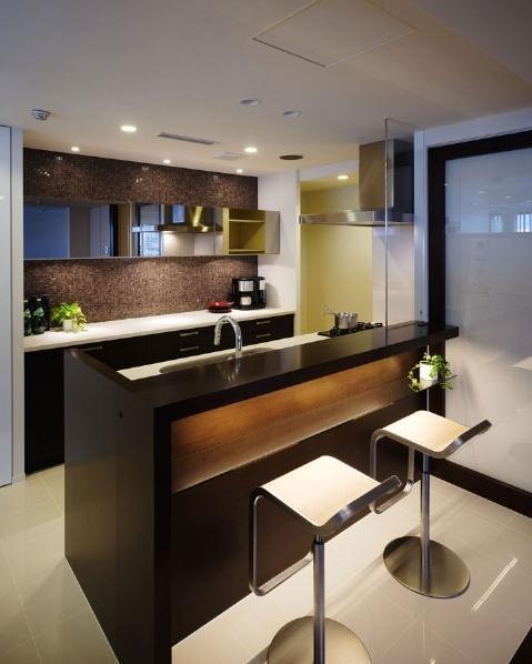 リビングの移動と拡大で、眺望や邸内の見通しが向上。光が行き渡るくつろぎの住まい。キッチンカウンターの脇には、家電収納を設置。キッチン側からはよく見える場所に配し、使い勝手を向上させながら、リビング側からは見えないように配慮されている。背面には、鏡張りの釣り戸棚と天井までの収納を設け、キッチン用品をすっきりと収められるようにした。