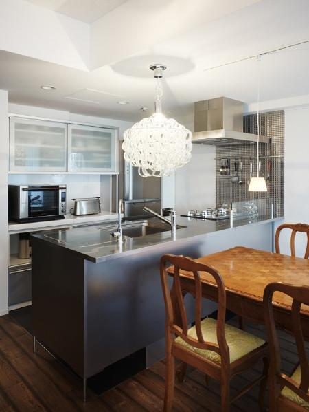味わいある素材や年月を経たような加工でアンティーク家具などの個性が引き立つ空間に。キッチンはご希望の対面スタイルにして、明るく開放的に。ステンレスのキッチンに合わせ、サイドにもメタリックなタイルを張り、クールな印象に仕上げた。華やかなシャンデリアやクラシカルなダイニングテーブル、椅子が調和して、モダンな中に落ち着いた心地よさも感じさせている。