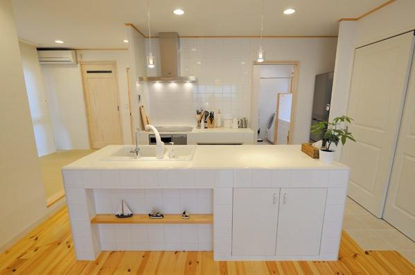 住空間の真ん中にアイランドシンクをレイアウトしたキッチンプラン。パイン材の床に映える真っ白なタイルのキッチンは、デザインもサイズもYさんの使い勝手に合わせて造作したもの。写真右の壁面には、パントリーと食器棚を兼ねた大容量の収納スペースが組み込んであるので、いつでもすっきりと片付いた空間に。シンクと水栓金具は米国コーラー社製。