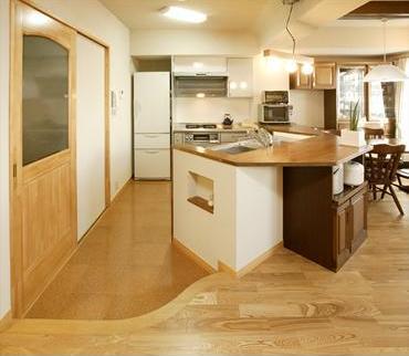 リビングの床レベルから一段下げて、カウンターキッチンを斜めに配置している。これは遮音等級の関係でリビングのフローリングを底上げ処理したためだが、「まるで舞台のよう」と、奥さまも大満足のご様子だ。またキッチン部分の床には、滑りにくくクッション性の高いコルク材を使用している。