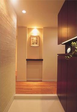 玄関はお気に入りの絵を飾る場。壁には質感が柔らかく、消臭作用もある珪藻土を。マンションのため広いスペースをとることは難しいが、コンパクトな空間を活かし、使いやすくまとめられている。写真右側のシューズクロークは天井高で収納力たっぷり。ご夫婦の靴をまとめて片付けることができる。また、左側の壁は消臭作用・調湿作用のある珪藻土を使っている。