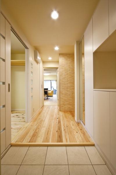 家族の一体感を大切にしながら素材にもこだわった、将来まで見据えた住まい。玄関はスペースを広げタイル貼りに。入って正面に見える壁には、調湿性に優れたエコカラットを採用。タイル調のデザインが、シンプルな色合いでまとめられた空間のアクセントになっている。