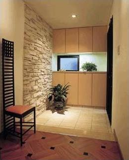 無垢の床材、漆喰の壁。自然素材で手仕事の感じられる仕上げに。人造石の壁面と大理石のたたきが重厚な雰囲気を醸し出している玄関。正面に見えるオリジナルの玄関収納の扉は床材の色に合わせてアイボリーピンクに。マッキントッシュのハイバックチェアーが空間を引き締めています。