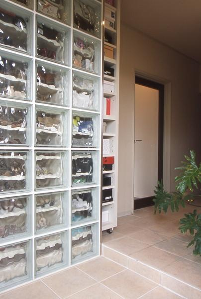 建物の構造上の制約も、上手な素材選びでクリアしたカフェのようなくつろぎ空間。玄関の扉を開けてまず目に飛び込んでくるのが、このガラスブロック。背部には、写真のように引き出せる靴箱が収まっている。土間まで貼り込んだタイルは、空間に広がりを持たせることに成功している。廊下には優しい光を放つ、フットライトが。