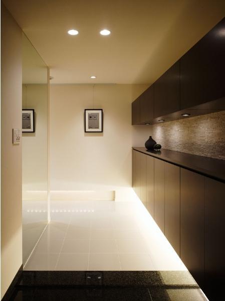 リビングの移動と拡大で、眺望や邸内の見通しが向上。光が行き渡るくつろぎの住まい。上下に配したシューズクロゼットは、空間に合わせてウォールナットでデザインしたオリジナル。足元の間接照明が、限られた空間に広がりや明るさを与えている。ホールから廊下にかけては、大判のタイルを採用。既存の御影石の玄関と調和させるとともに、さわやかな印象を醸し出し、重厚感のある邸内と差をつけた。