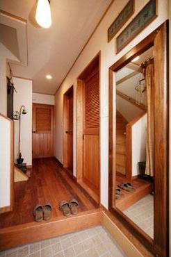 玄関のドアを開けて一歩足を踏み入れると、そこにはアジアンテイストの空間が広がる。無垢材のチークを敷いた床、木絹壁紙の壁、モールディングが印象的な大きなミラー。そしてルーバー付きの扉は、インテリアに合わせてすべてオリジナルで製作したものである。自然素材をふんだんに使用。統一感を重視した、細部にまでこだわりを感じる仕上がりになっている。