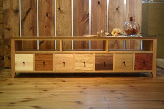 オーク無垢材の天板を使って、高級感と、7種類の木材を使い、色分けした抽斗前板をしつらえて、カジュアルな印象のテレビボードを作りました。7種類の木材それぞれに収納するものを変えて、使い分けることができます。無垢材を天板と脚に使い、側板と方立ち、中棚には天然木オーク柾目突き板のフラッシュ材を使い分けています。健康に配慮したFフォースター(F☆☆☆☆)規格!工場直売ネットオリジナル!熟練の職人と若い職人が丹精込めて作っています
