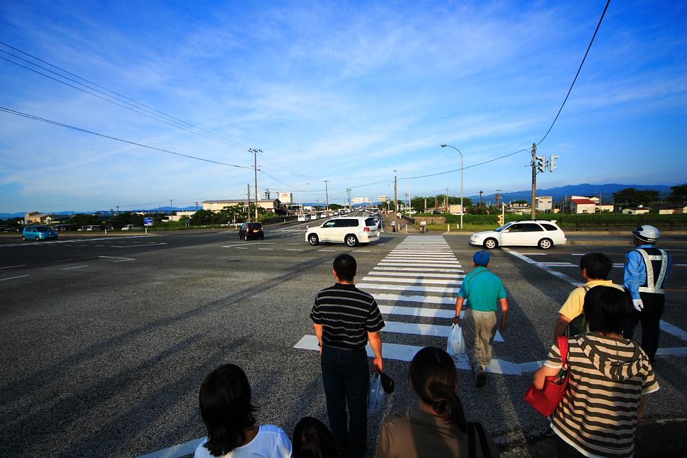 筋雲が広がる鶴岡市内。足早に河川敷へ向かう人達。