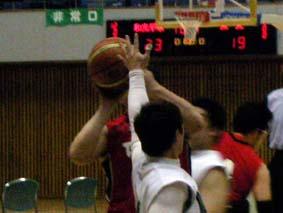 赤いユニフォームの選手がシュートをはなつところ_白いユニフォームの選手が前でプレッシャーをかけているところ
