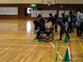 車椅子に乗車するときに、友達が車椅子を抑えている場面