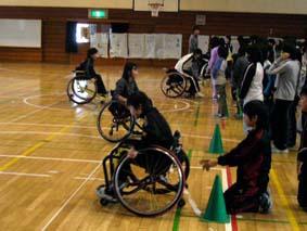 小学生が車椅子をこいでいる場面