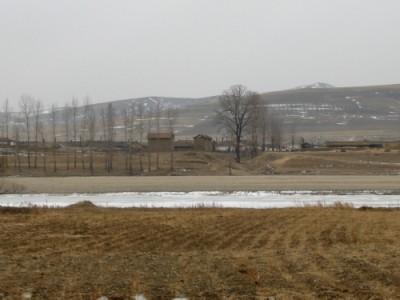 中国から、豆満江(凍結中)を挟んで対岸に北朝鮮の農村を望む