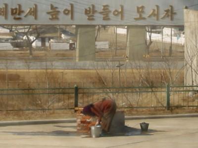 ◆公共施設の中庭で水をくむ住民=北朝鮮北部で
