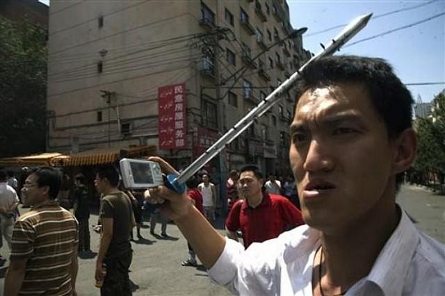 手に凶器とデジカメをもつ中国人の暴徒
